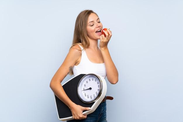 Jeune fille blonde avec une machine de pesage et avec une pomme sur un mur blanc bleu isolé Photo Premium