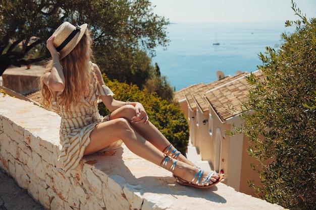 Jeune Fille Blonde En Robe D'été Regardant La Mer Turquoise Photo Premium
