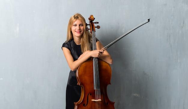 Jeune fille blonde avec son violoncelle sur fond de mur texturé Photo Premium
