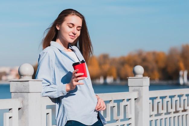 Jeune fille blonde souriante tenant une tasse de café Photo gratuit