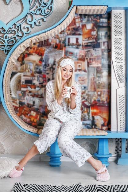 Jeune fille boit du café en pyjama et pantoufles. masque de sommeil Photo Premium