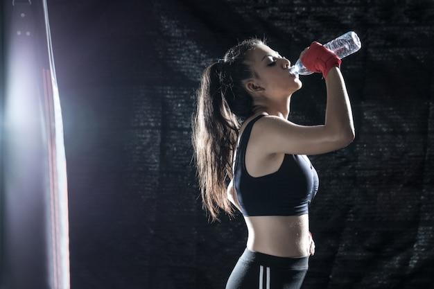 La jeune fille boit de l'eau pendant qu'elle se repose après l'entraînement de boxe au gymnase. Photo Premium
