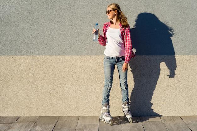 Jeune fille avec une bouteille d'eau, chaussée de rouleaux Photo Premium