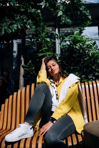 Jeune Fille Brune Assise Sur Un Banc Dans La Partie Centrale De La Vieille Ville. Photo gratuit