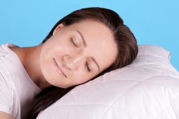 Jeune Fille Brune Dormir Sur Un Oreiller Blanc, Les Yeux Fermés. Isolé Sur Fond Bleu. Photo Premium