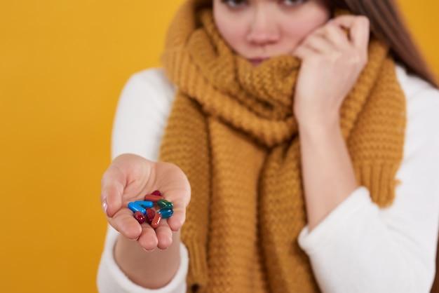 Jeune fille brune a froid, pose avec des pilules isolées. Photo Premium