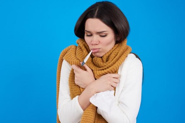 Jeune fille brune a froid prenant la température Photo Premium