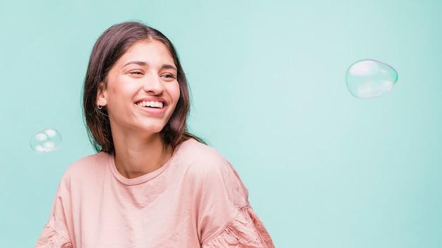 Jeune fille brune jouant avec des bulles de savon Photo gratuit