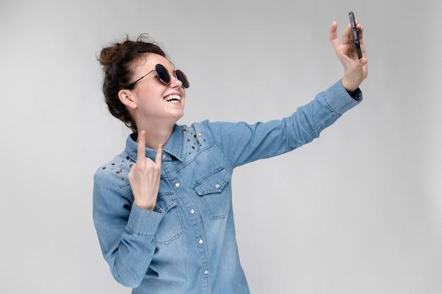Jeune fille brune à lunettes rondes. les cheveux sont rassemblés en un chignon. fille avec un téléphone noir. la fille fait selfie. Photo Premium