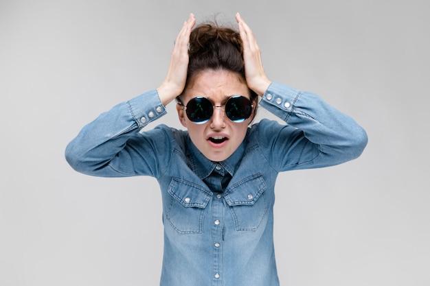 Jeune fille brune à lunettes rondes. les cheveux sont rassemblés en un chignon. la fille tient ses mains derrière sa tête. Photo Premium