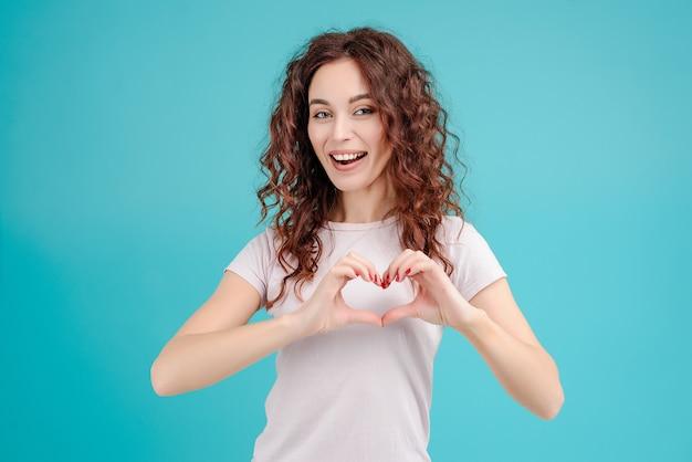 Jeune fille brune montrant le coeur avec ses mains isolées Photo Premium