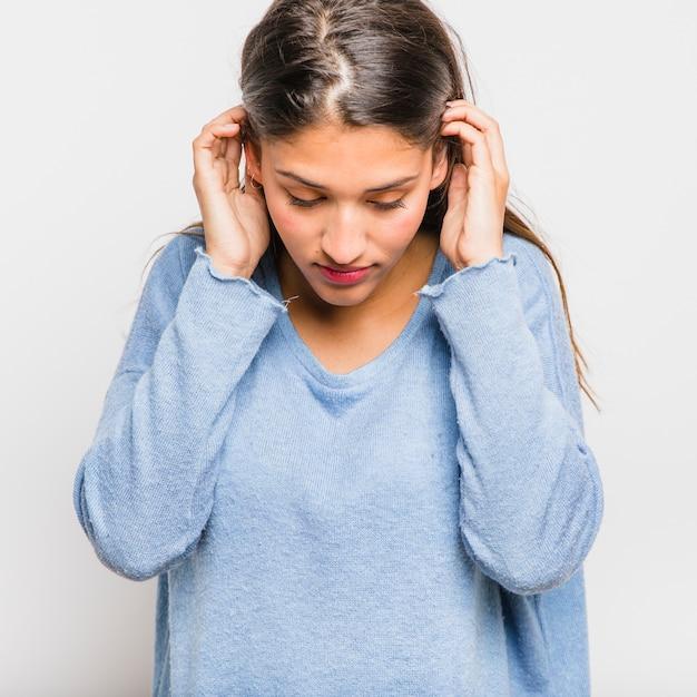 Jeune fille brune posant avec un pull bleu Photo gratuit