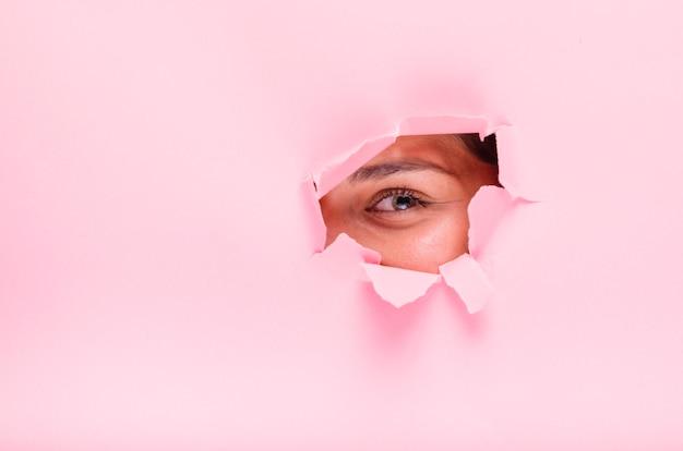 Jeune fille brune posant à travers un trou de papier Photo gratuit