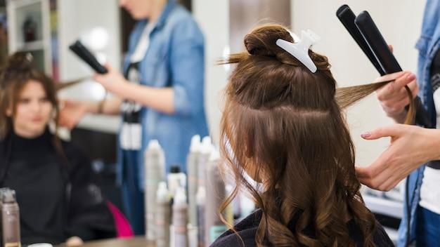 Jeune fille brune se fait coiffer Photo gratuit
