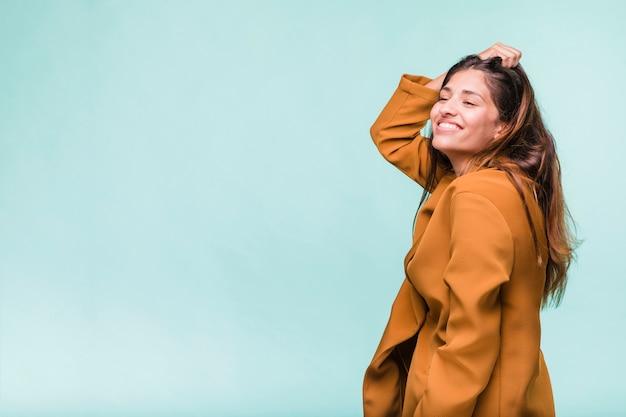 Jeune fille brune souriante posant avec manteau Photo gratuit