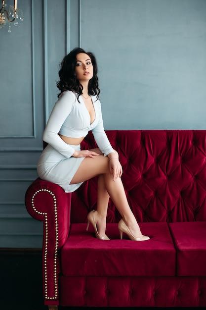 Jeune fille brune vêtue d'une robe bleue et talons hauts, assise sur un canapé bordeaux. Photo Premium