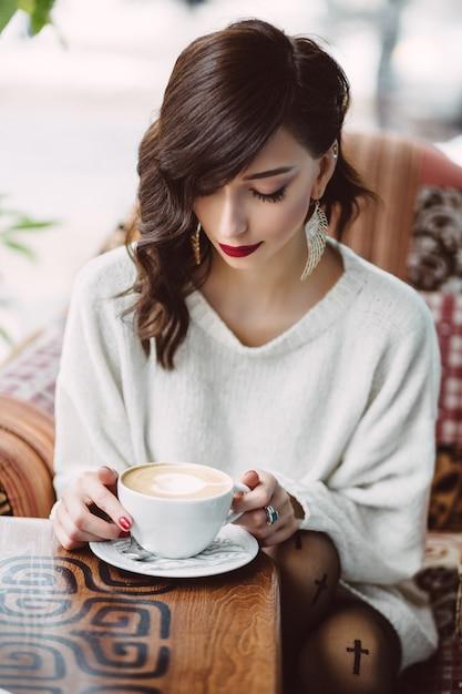 Jeune fille buvant du café dans un café branché Photo gratuit