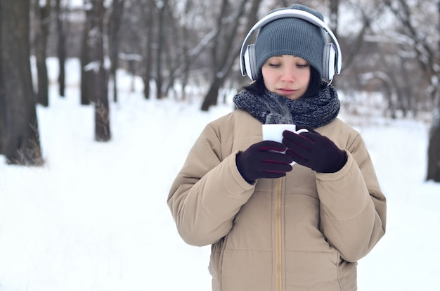 Jeune fille avec un casque et une tasse de café Photo Premium