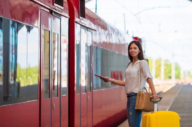 Jeune fille caucasienne avec des bagages à la gare voyageant en train Photo Premium