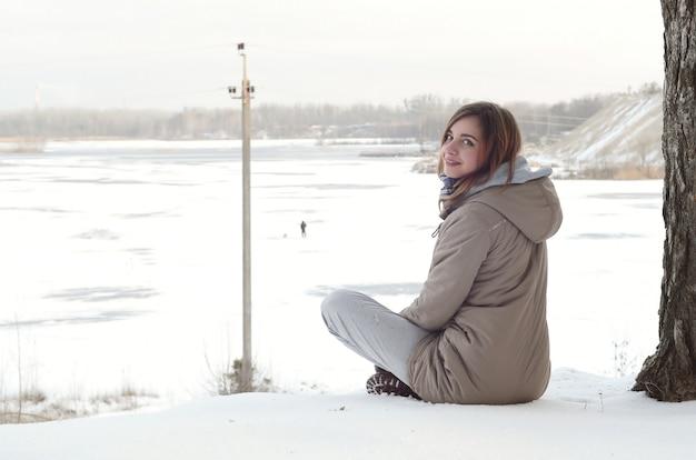 Une jeune fille caucasienne dans un manteau brun est assise près d'une falaise Photo Premium