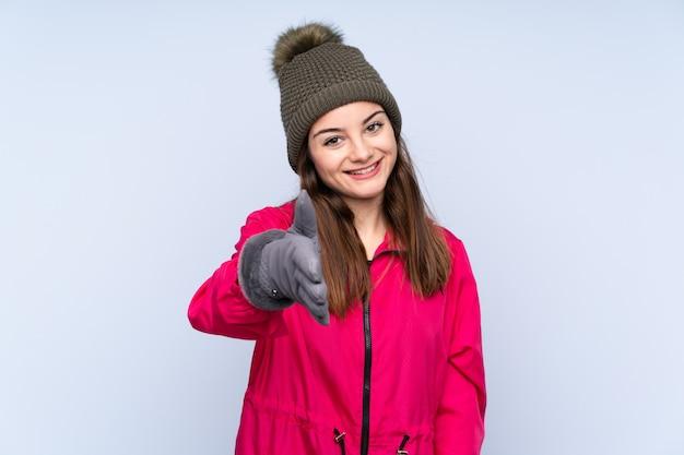 Jeune Fille Avec Un Chapeau D'hiver Sur Le Mur Bleu Se Serrant La Main Pour Fermer Une Bonne Affaire Photo Premium