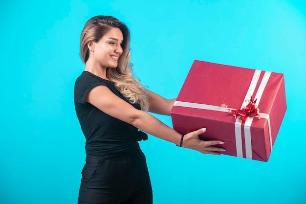 Jeune Fille En Chemise Noire Tenant Une Grande Boîte-cadeau Et Se Sent Positif. Photo gratuit