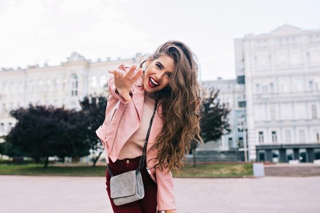 Jeune Fille Avec Une Coiffure Longue S'amusant En Ville. Elle A Un Pantalon Vineux, Une Veste Rose, Se Penche Vers La Caméra. Photo gratuit