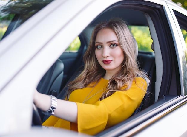 Une jeune fille conduit une voiture. Photo Premium