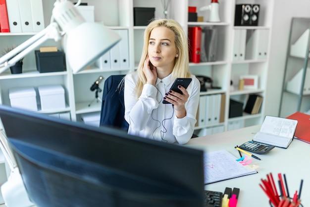 Une Jeune Fille Dans Le Bureau Est Assise à Un Bureau, Tenant Un Téléphone à La Main Et Parlant à Travers Un Casque. Photo Premium