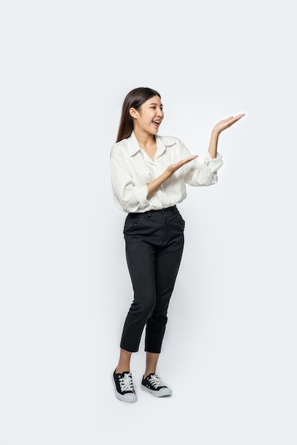 La Jeune Fille Dans Une Chemise Blanche Et Le Signe De La Main Ouverte Sur Le Côté Photo gratuit