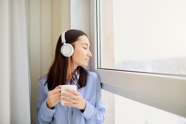 Une Jeune Fille Dans Les écouteurs Avec Une Tasse De Boisson Chaude Dans Les Mains Près De La Fenêtre. Photo Premium