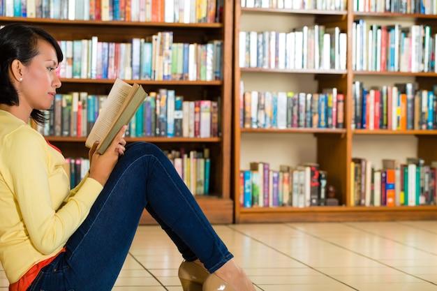 Jeune fille dans un livre de lecture de bibliothèque Photo Premium