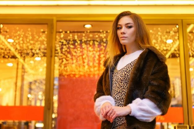 Jeune Fille Dans Un Manteau De Fourrure Posant Pour L'ambiance Festive De La Caméra Photo Premium