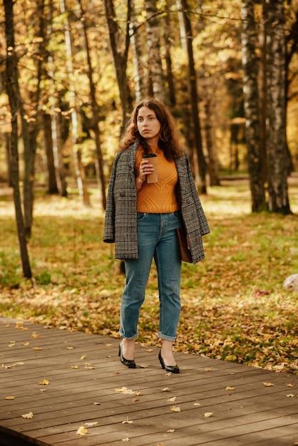 Une Jeune Fille Dans Un Manteau Se Promène Dans Le Parc D'automne Photo Premium