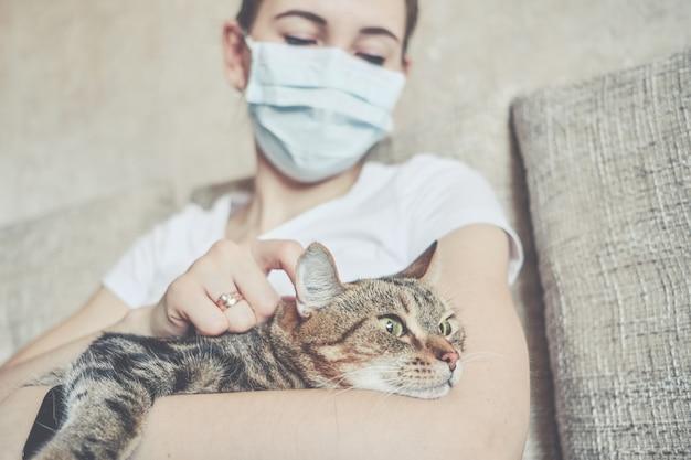 La Jeune Fille Dans Un Masque Médical Est En Auto-isolement à La Maison Et Se Repose Avec Un Chat Sur Le Canapé. Photo Premium
