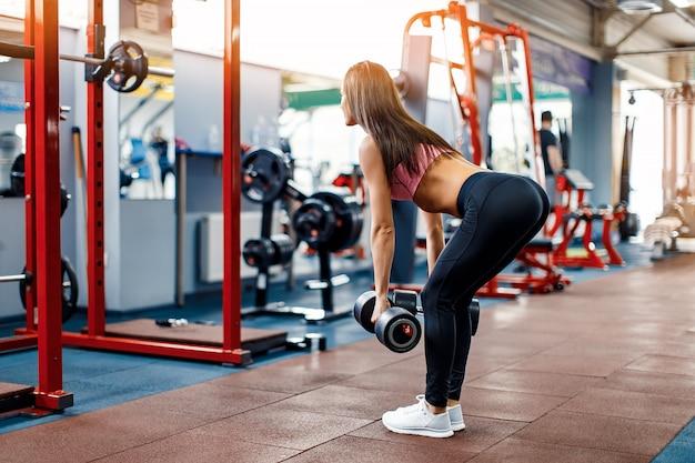 La jeune fille dans la salle de gym s'accroupit avec une barre. Photo Premium