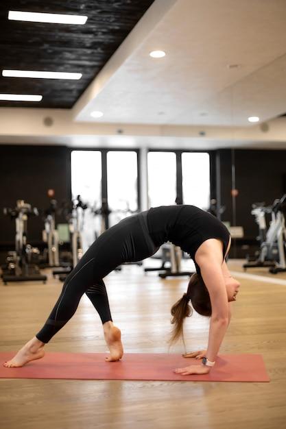 La jeune fille dans la salle de sport fait du yoga pour se maintenir en forme ou contrôler son excès de poids. Photo Premium