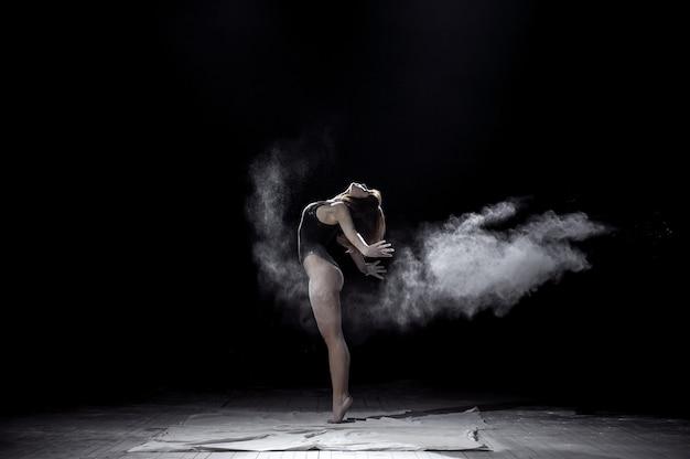 Jeune fille dansant avec une farine sur fond noir Photo Premium