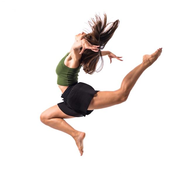 Jeune fille dansant et sautant en studio sur fond isolé Photo Premium