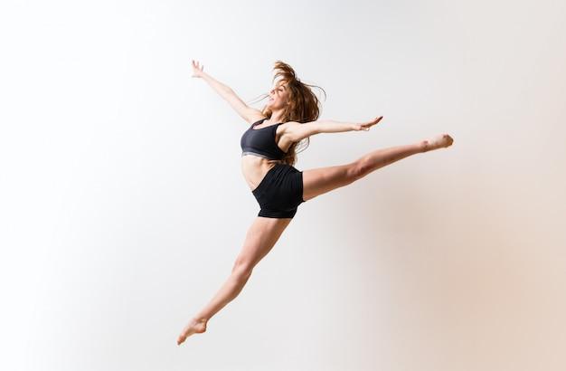 Jeune fille danse sur mur blanc isolé Photo Premium