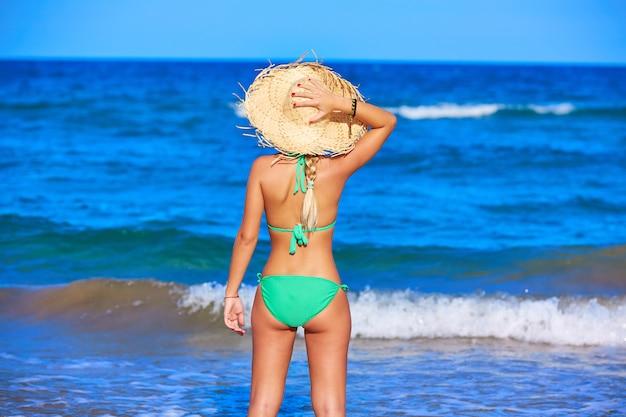 Jeune fille debout en regardant le chapeau de plage de la mer Photo Premium