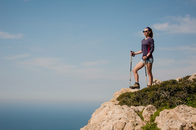 Jeune fille debout sur le rocher en short avec des cannes Photo Premium