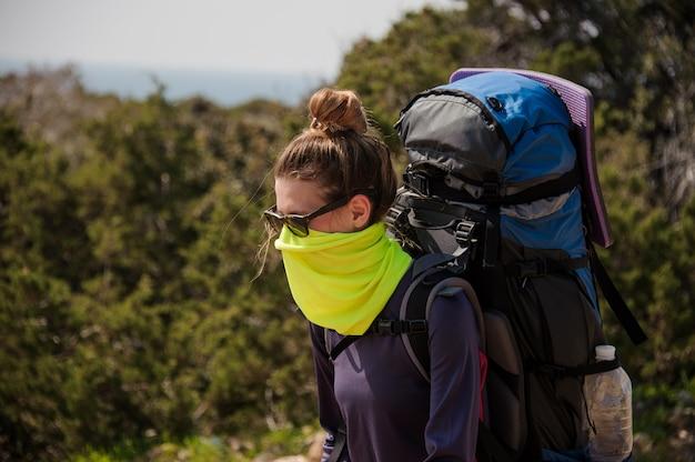 Jeune fille debout avec un sac à dos de randonnée et un masque spécial contre la poussière Photo Premium