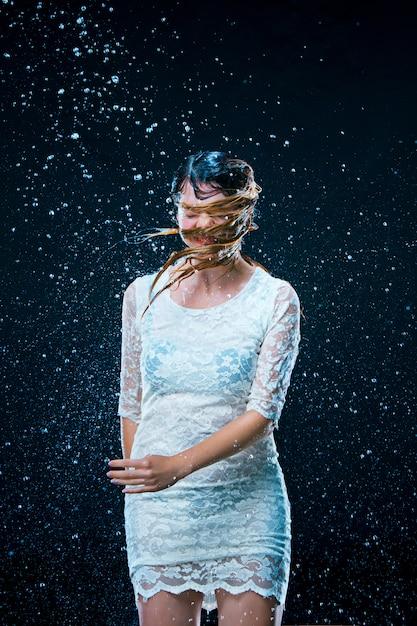 La Jeune Fille Debout Sous L'eau Courante Photo gratuit