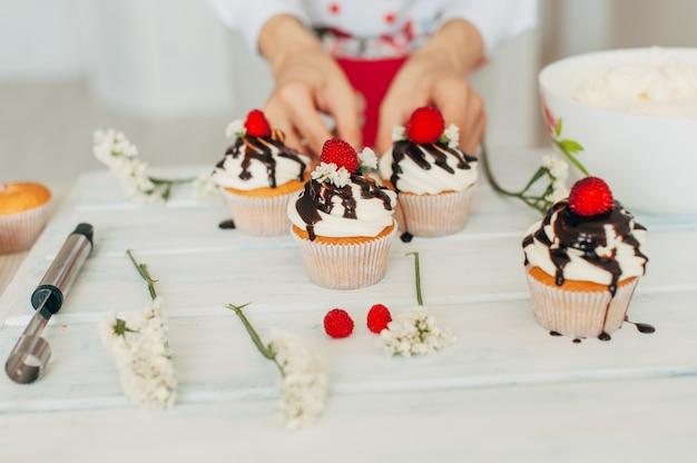 Une jeune fille décore des petits gâteaux avec des baies fraîches et des fleurs Photo Premium
