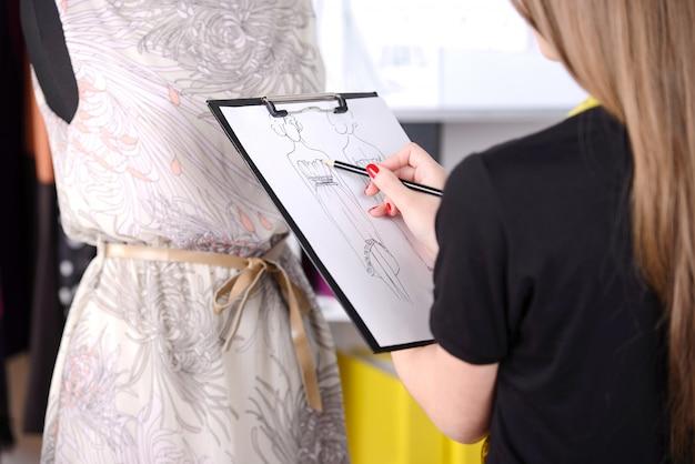 Jeune fille dessine une robe sur papier en studio. Photo Premium