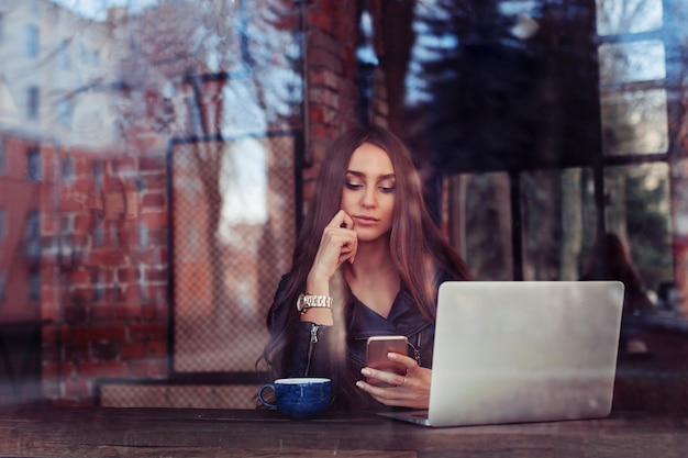 Jeune fille devant la fenêtre dans un café travaillant à l'ordinateur Photo Premium