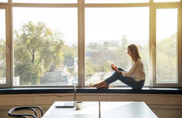 Une Jeune Fille Du Millénaire Regarde Dans Un Smartphone Tout En étant Assis Près De La Fenêtre Dans Un Intérieur Lumineux. Photo Premium
