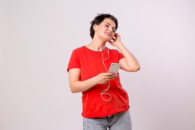 Jeune fille écoutant de la musique au téléphone et dansant Photo Premium