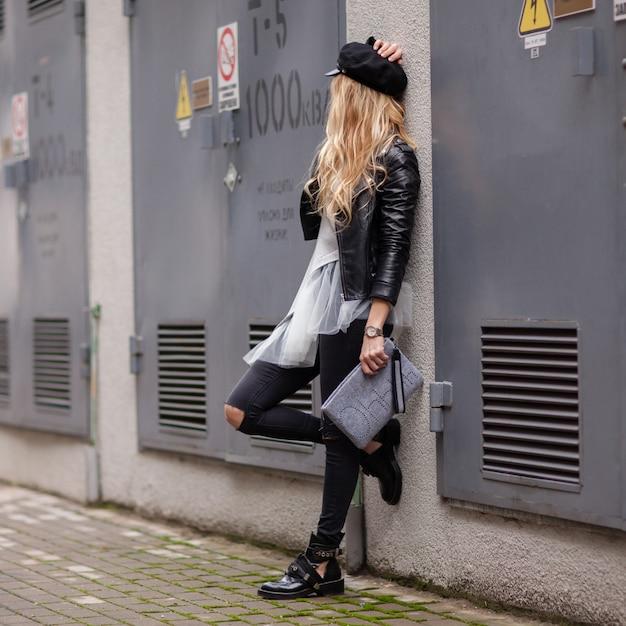 La Jeune Fille élégante Dans Une Veste En Cuir Noir Avec Un Sac à Main Gris Dans Ses Mains Regarde Loin Photo Premium